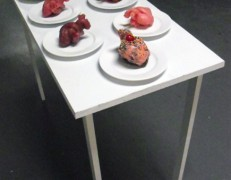 Melissa Huang, Eat Your Heart Out, 2012, wood table, porcelain plates, six wax hearts, one chocolate and frosting heart, one bronze heart